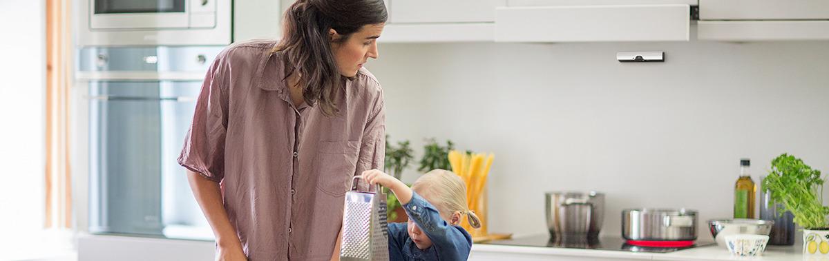 Une jeune maman regarde par-dessus son épaule vers SécuriPlaque, le dispositif de prévention des incendies pour la plaque de cuisson